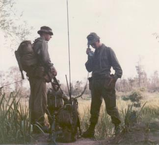 "The executive officer of Company ""D"", 5th Battalion, Royal Australian Regiment, looks on whilst his radioman requests helicopter extraction."
