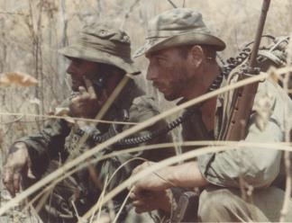 A Platoon Sergeant and Radio Telephone Operator (RTO) of 8th Platoon, 'C' Company, 7 RAR, pause during an ambush patrol in the Nui Thi Vai hills.