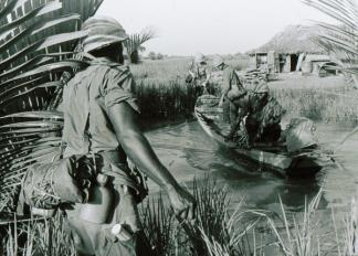 9th Infantry Division soldiers use a local sampan to cross a river near Long An in the Mekong Delta.