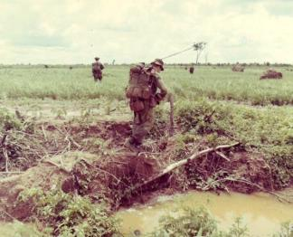 A heavily laden member of Co 'B', 2nd Royal Australian Regiment, crosses a ditch during a search and clear operation.