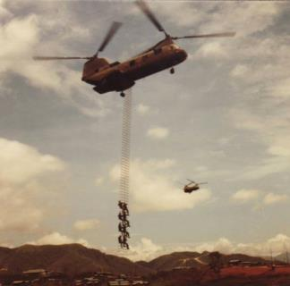 ARVN Rangers climb a long extraction ladder suspended from a hovering CH-46 Helicopter.