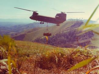 A CH-47 Chinook sling lifts supplies for members of Co A, 1st Bn, 8th Inf, 4th Inf Div, on the side of Hill 1049, approximately 8km southeast of Dak To in the Central Highlands.