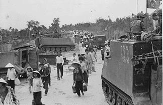 M-113 Armored Personnel Carriers of the 5th Battalion, 60th Infantry, 9th Infantry Division stand by as villagers evacuate My Tho in the Mekong Delta during the 1968 Tet Offensive.