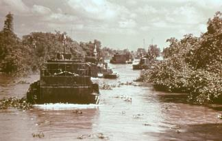 A column of Armored Troop Carriers (ATC) head down a hibiscus choked river in the Mekong Delta.