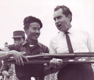 Brigadier General Nguyen Thi, commander of the Vietnamese I Corps, presents a captured Viet Cong rifle to Richard Nixon.