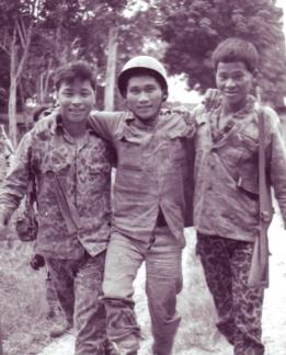 "A wounded CIDG Strike Force member is helped to the medical aid station at Ap Suoi by his comrades after a fire fight with the Viet Cong in War Zone ""D""."