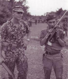 "Special Forces Captain Edward Rybat and Vietnamese Lieutenant Huyen Phuoc Thoi use the radio to call in troops during a mission against the Viet Cong in war zone ""D""."