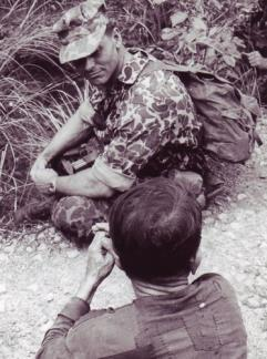 "Special Forces Captain Edward Rybat looks at a Viet Cong suspect captured during mission in war zone ""D"", north of Ben Cat (III Corps)."