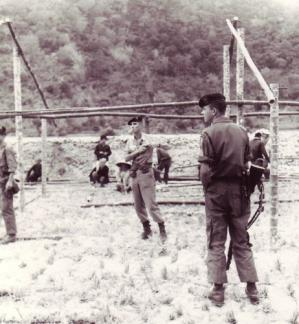 Members of the A-14 Team, 5th Special Forces Detachment, observe the construction of the CIDG camp at Chau Lang, An Giang province, Mekong Delta (IV Corps).