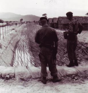 Sergeants Larry Manes and Raymond Echevarria of the A-14 Team, 5th Special Forces Detachment, inspect the punji stake defenses at the Chau-Lang CIDG camp in An Giang province, Mekong Delta (IV Corps).