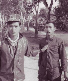 "A CIDG Strike Force member leads a captured Viet Cong guerrilla after a firefight at Bau Bang hamlet in war zone ""D""."