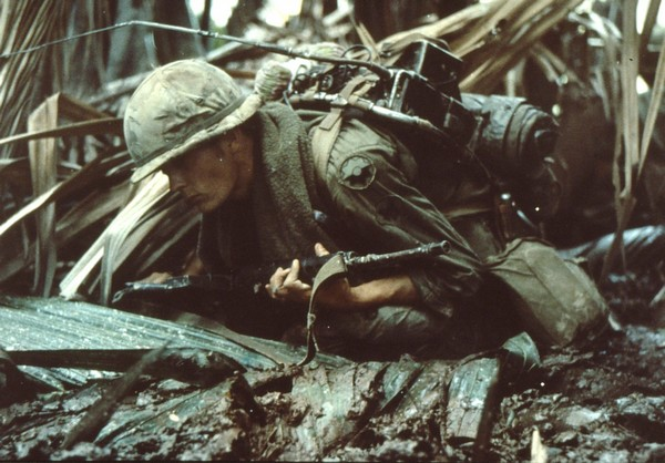 A Radio Telephone Operator (RTO) of the 9th Infantry Division takes evasive action whilst on an operation in the Mekong Delta.