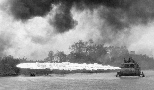 An early flame-throwing Tango Boat (ATC-92-2) unleashes its deadly fire on the riverbank near Dong Tam in the Mekong Delta.