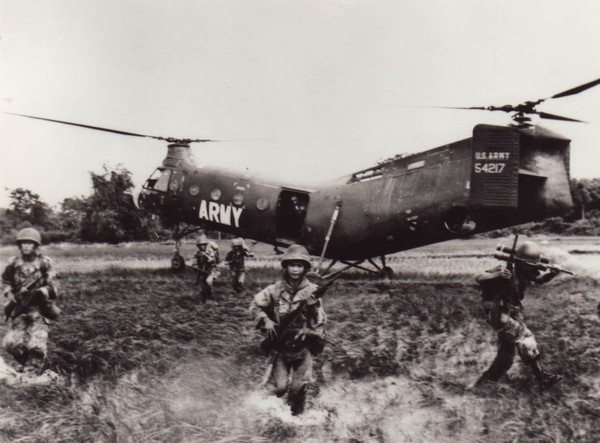 After leaving their CH-21 helicopter ARVN soldiers slog through the water of a rice paddy to begin an attack on the Viet Cong.