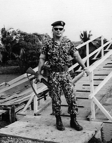 First Lieutenant Rick Caplin, XO of Special Forces Detachment A-321, stands by a wooden bridge over the canal at Vinh Binh in the Mekong Delta.