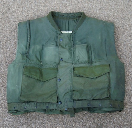 The 2nd version of the Marine Corps M1955 vest had a zip front closure, an integral cartridge belt holder, a rifle guard over the right shoulder and two lower cargo pockets.
