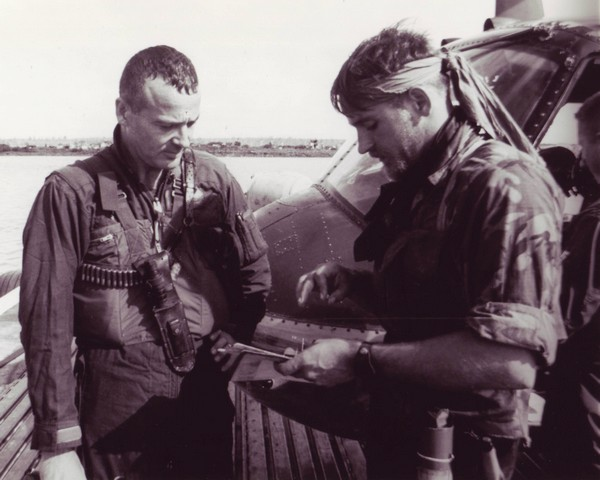 A SEAL team member confers with Lieutenant Commander Roland F.