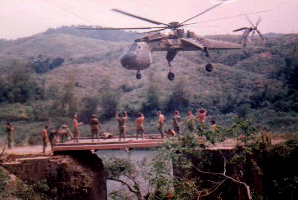 A CH-54 Sikorsky Skycrane delivers a bridge to route 9, 4-1/2 miles from Khe Sanh (I Corps).