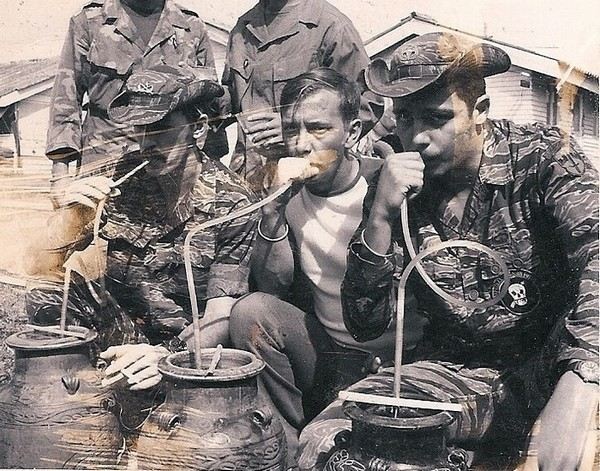 Special Mission Force (SMF) members Ferricks, Brown and Curtis (left to right) drink rice wine at a Montagnard party.